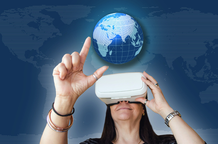 worldmap: A woman touching a worldmap while enjoying a 3d experience. Vr headset is a gadget to use with a mobile phone