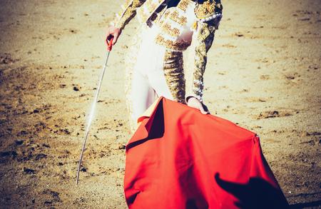 bullfight: A bullfighter with estoque and muleta giving a pass in the bullring. Corrida de toros