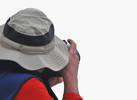 photography session: Paparazzi isolated over white. Unrecognizable photographer with a hat about to take pictures hidden under a big hat.
