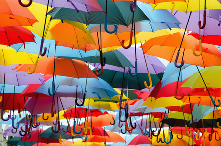 hundreds: Bright colorful hundreds of umbrellas floating above the street Stock Photo