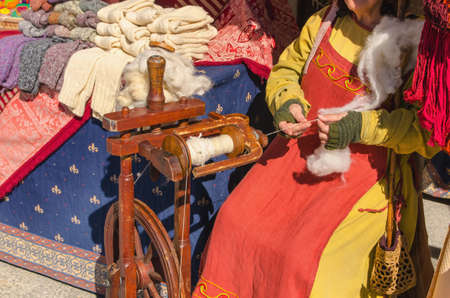 spinning wheel: Unrecognizable senior woman spinning on ancient wooden spinning wheel