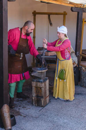 smithery: ARROYOMOLINOS, MADRID, SPAIN - APRIL 9, 2016: blacksmith and a assistant working with iron in the forge. Old techniques demonstration in a medieval fair Editorial
