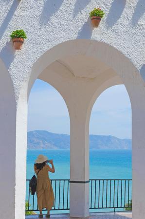 balcon: Unrecognizable tourist making photo of seascape in Balcon de Europa, Nerja, Malaga, Andalusia, Spain