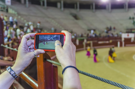 unrecognizable person: Unrecognizable person taking video of corrida performance