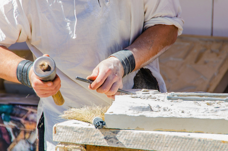 sculpting: Faceless man working with chisel. Sculpting on stone