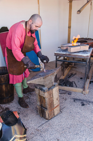 smithery: ARROYOMOLINOS, MADRID, SPAIN - APRIL 9, 2016: smith working with iron in the forge. Old techniques demonstration in Arroyomolinos medieval fair Editorial