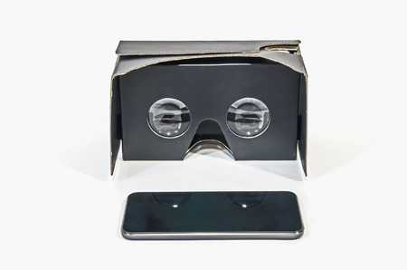 mobile headset: Cardboard virtual reality glasses in black with a mobile phone. Vr headset made with cardboard Stock Photo