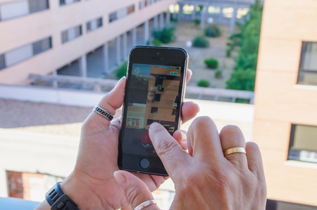 nintendo: LEGANES , MADRID, SPAIN - JULY 25 , 2016: A woman trying to capture a character in Pokemon Go mobile game. Pokemon Go is a GPS based augmented reality mobile game with Nintendo pokemon characters. Editorial