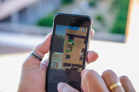 nintendo: LEGANES , MADRID, SPAIN - JULY 25 , 2016: A woman holds a mobile phone with pokemon go app trying to capture a character. Pokemon Go is a GPS based augmented reality mobile game with Nintendo pokemon characters.