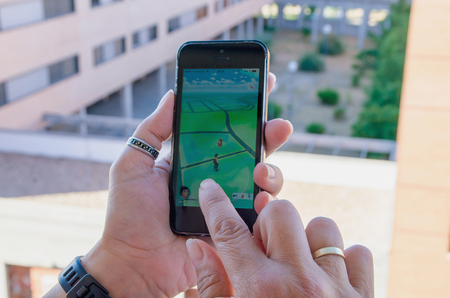 nintendo: LEGANES , SPAIN - JULY 25 , 2016: A woman holds an iphone with pokemon go app. Pokemon Go is a GPS based augmented reality mobile game with Nintendo pokemon characters.
