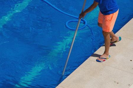 mantenimiento: Un hombre limpia la piscina con una red. servicio de mantenimiento de Verano