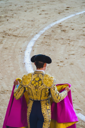 capote: A bullfighter holding his capote and awaiting for the bull in the bullring. Corrida de toros