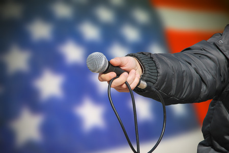 preferred: Presidential election survey. Hand holding microphone against an american flag asking about preferred government