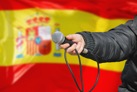 Presidential election survey. Hand holding microphone against an spanish flag asking about preferred government