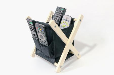 Alcuni telecomandi in un contenitore di tessuto nero da utilizzare con diverse apparecchiature digitali o elettroniche. Intrattenimento domestico
