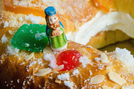 gaspar: Detail on a kings cake and a figurine that can be found hidden into it. Roscon de reyes or rosca de reyes with surprise. Gaspar, Caspar Stock Photo