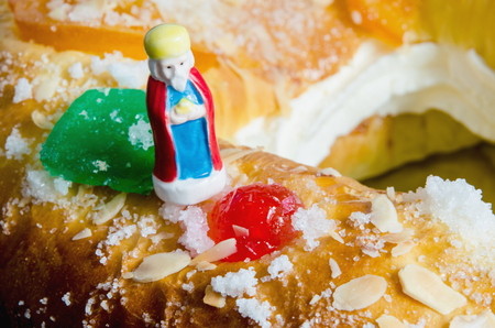 melchior: Detail on a kings cake and a figurine that can be found hidden into it. Roscon de reyes or rosca de reyes with surprise. Melchor, Melchior.
