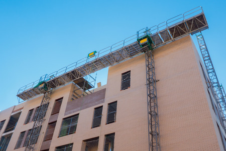 Mechanical scaffolding used in buildings construction. Modern equipment to elevate workers and materials mechanically Stock Photo