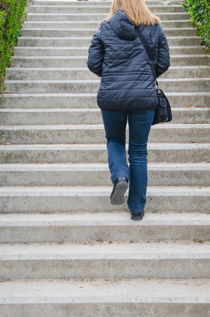upstairs: Back view of woman going upstairs. Unrecognizable Stock Photo