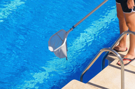 A man in shorts cleaning the swimming pool with a net. Summer pool maintenance service
