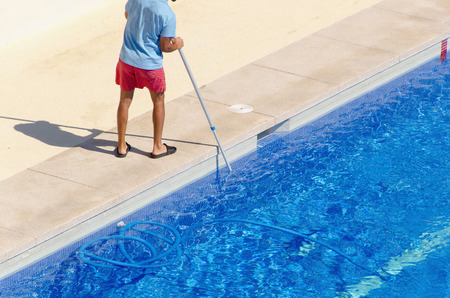 A guy cleaning the swimming pool ground with a vacuum head. Summer pool maintenance service