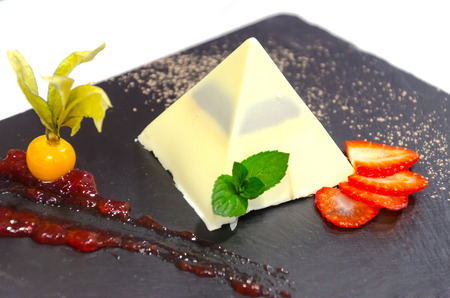 sweetstuff: white chocolate pyramid in a black plate with strawberry slices, golden berries and jam Stock Photo