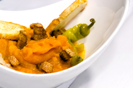 Plate of mashed potatoes with torreznos and hot green peppers. Known in spain as patatas machaconas or revolconas