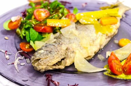 Detail on a pickled trout with assorted vegetables. Typical spanish recipe of freshwater fish. Salmoninae, Salmonidae