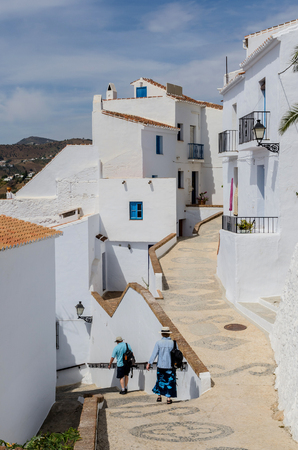 Two people walking on the streets of frigiliana. Typical andalusian town with houses painted in white. Costa del Sol, Malaga, Andalusia, Spain,