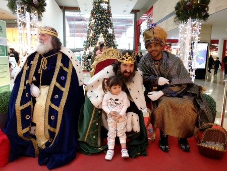 MADRID, SPAIN - DECEMBER 28: Reyes Magos. Three wise men with a little girl posing for picture in a shopping centre in December 28, 2017 in Leganés, Madrid, Spain. Spanish tradition tells that Melchior, Caspar and Balthazar receive letters from children