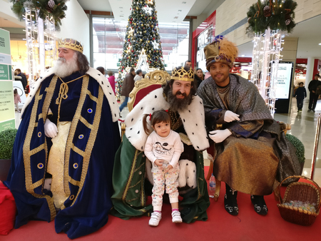 MADRID, SPAIN - DECEMBER 28: Three wise men with a little girl posing for picture in a shopping centre in December 28, 2017 in Leganés, Madrid, Spain. Spanish tradition tells that Melchior, Caspar and Balthazar receive letters from children and so bring Editorial
