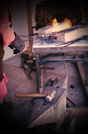 smith working with iron in the forge. Old techniques in craft work. Vignette effect