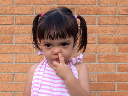 Little girl sticking a finger in her nose wearing a white and pink stripes dress