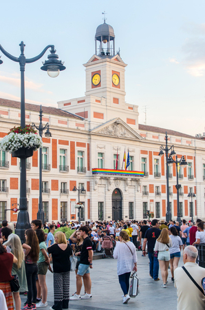 MADRID, SPAIN - JUNE 29, 2018: People in puerta del Sol in Madrid. Real casa de Correos is decorated with gay flag during gay pride week Editorial