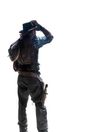 rear view of a cowboy with saddlebag on his shoulder taking off his hat Zdjęcie Seryjne