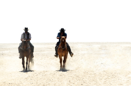 Two cowboys riding horses on a sandy ground isolated over white. one of them is the sheriff. Two horsemen Reklamní fotografie