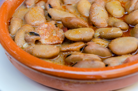 Michirones. Broad beans boiled with chorizo, cured ham and bacon served in a clay plate. Vicia faba