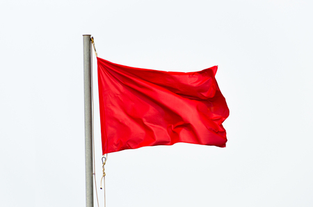 Red flag waving on the wind isolated over white.