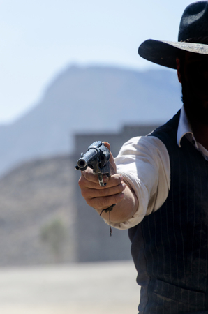 cowboy aiming with his pistol or gun