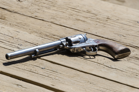 detail on a revolver or pistol placed onto a wooden ground