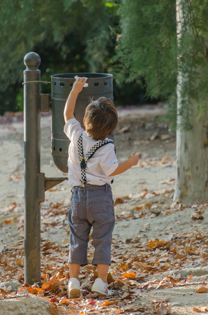 Well educated little boy wearing suspenders throwing away some waste in the trash container at the park Archivio Fotografico
