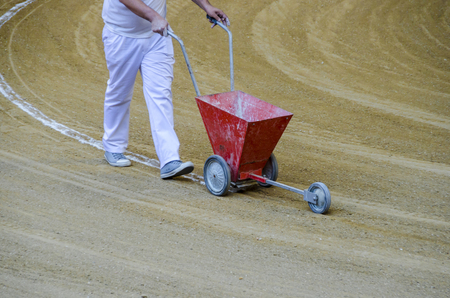 Arenero painting white lines in a bullring with a typical cart.