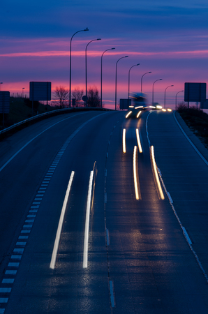 Night traffic with light trails in a freeway at morning