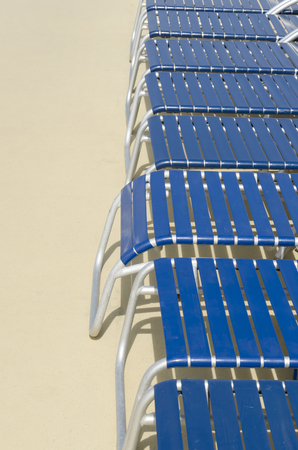 Some lounge chairs in blue to sunbathing placed in a yellow ground Imagens - 117713299