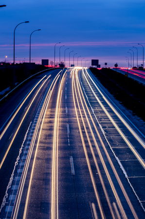 Fast traffic in the speedway at night with vehicle light trails Imagens - 117713217