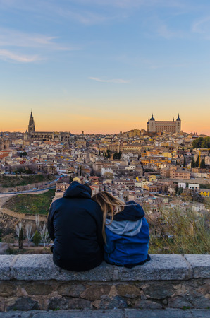 young couple enjoying the view of the city of Toledo at sunset Imagens