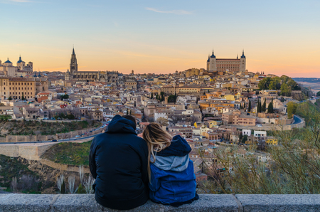 couple of lovers sitting and viewing a panoramic of the city of Toledo at sunset. Toledo is known as capital of three cultures, moorish, christian and jewish