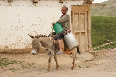 east riding: Hissar Mountains, Uzbekistan, May 2012: Man riding donkey