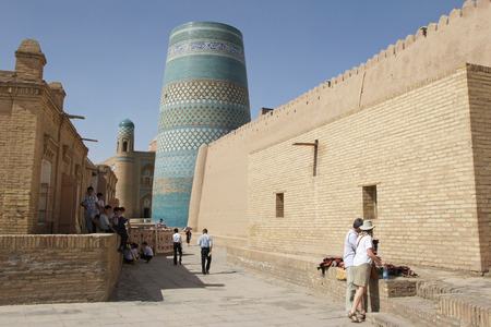 historic district: KHIVA, UZBEKISTAN - MAY 19, 2012: People in the historic district of Khiva with minaret Kalta Minor in the background on May 19, 2012 in Uzbekistan, Asia.                   Editorial