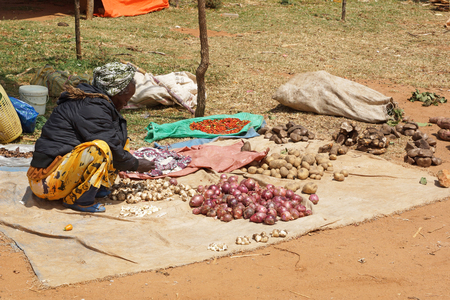 weekly market: KEY AFER, ETHIOPIA - NOVEMBER 20, 2014: Old woman selling vegetables on the weekly market in Key Afer on November 20, 2014 in Key Afer, Ethiopia, Africa.